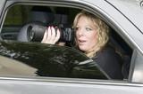 female private investigator with camera poster