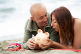 Budget holidays - young couple holding a piggy bank poster