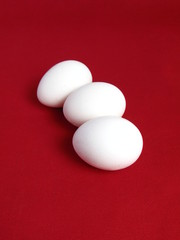 Group of three eggs on red background