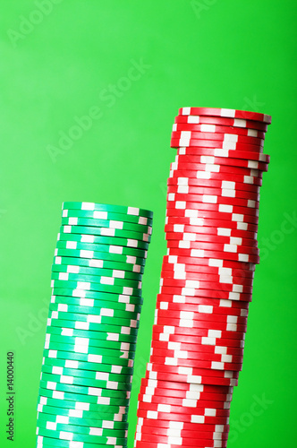 Stack of red and green casino chips against green background