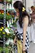 Junge Frau steht vor einem Blumenstand.
