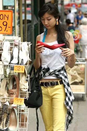 Junge Frau mit großer Freude beim Schuhe einkaufen.
