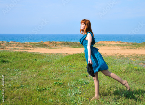 redheaded girl walking on the beach  toward sun