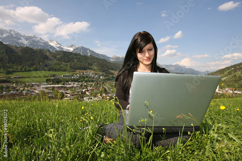 Mädchen mit Laptop in Wiese / Hintergrund Schladming
