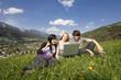 Junge Leute mit Laptop in Wiese / Hintergrund Schladming