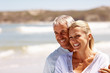 Happy mature couple embracing on a sunny day at the beach