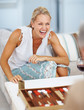 Happy mature woman playing backgammon