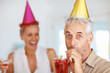 Elderly man having drink at a birthday party