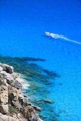 Gommone naviga tra le azzurre acque della Sardegna