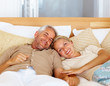Charming mature couple sleeping on the bed