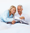 Portrait of an old couple in bed reading the morning newspaper