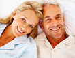Closeup of a smiling senior couple lying on bed, head to head