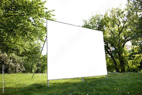 Leinwanddruck Bild leere Plakatfläche vor grünem Rasen