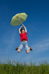 Girl holding umbrella jumping against blue sky