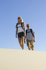 Couple Hiking through Sand Dunes