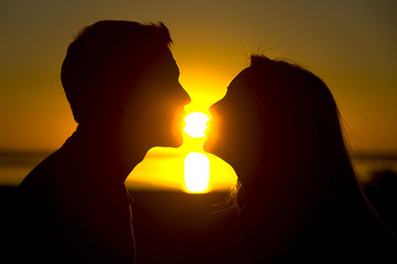 A couple about to kiss at sunset