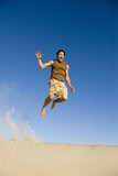 An attractive man jumping off a sand dune