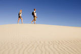 Hikers March Across Desert Sand Dune