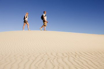 Hikers March Across Desert Sand Dune