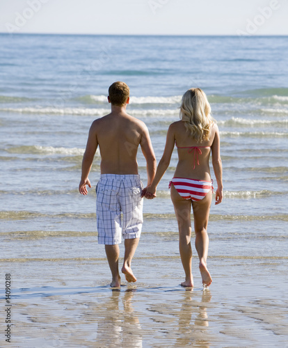 Stock Photo titled: Couple Holding Hands Running On Beach At Sunset In