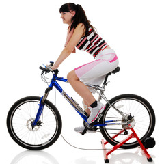 young woman exercising on a bicycle Isolated on white