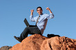 Young businessman connected to internet in desert
