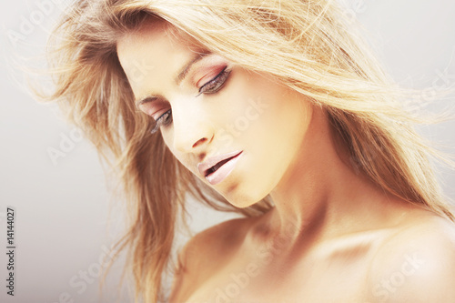 Beautiful blond girl with hair fluttering in the wind