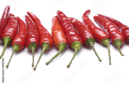 Red hot chili peppers aligned in rows over white background. © Mee Ting