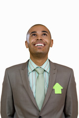 Businessman wearing arrow shaped post it on jacket, looking up, smiling, cut out
