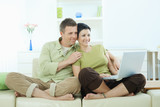 Couple browsing internet at home poster