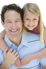 Girl with arms around father, smiling, portrait, cut out