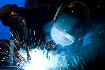 man at work: welder with spark arcing