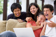 multi ethnic students laughing at something on laptop