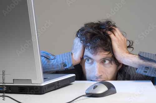 Man biting desk while looking at computer screen