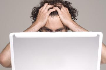 Man pulling at hair while looking at computer screen