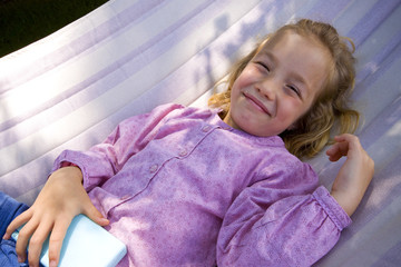 little girl plays with a portable game console in a hammock