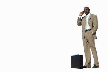 Businessman by briefcase using mobile phone, cut out