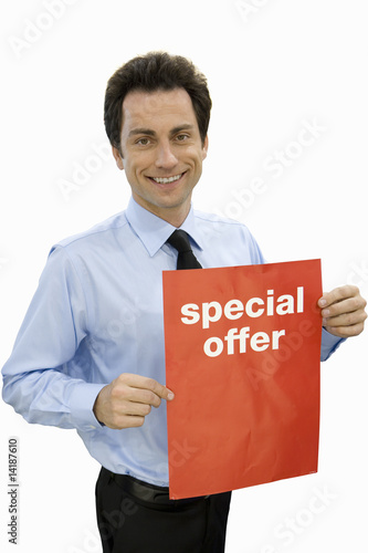 Young salesman with 'special offer' sign, smiling, portrait, cut out