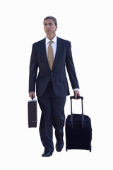 Businessman wheeling luggage, cut out