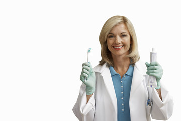 Female dentist holding toothbrush and toothpaste, smiling, front view, portrait, cut out