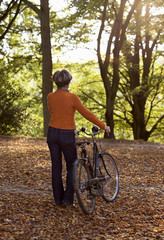 A senior woman pushing a bicycle through the autumn leaves