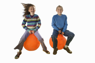 Girl and boy playing on inflatable hoppers, smiling, portrait, cut out