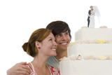 Young couple looking at wedding cake, smiling, cut out