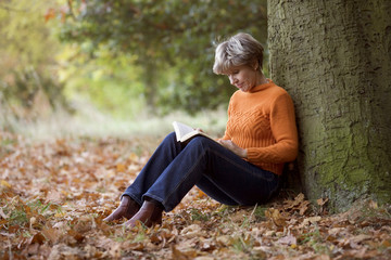 A senior woman sitting beneath a tree reading a book