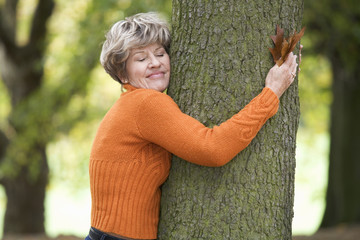 A senior woman hugging a tree in autumn time