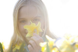 Young girl smelling yellow daffodil, cut out