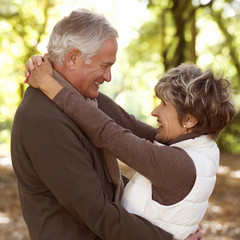 A senior couple embracing in autumn time