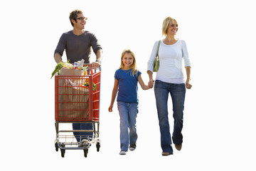 Man pushing shopping trolley, mother holding daughter's hand, smiling, front view, cut out