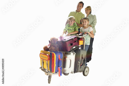 Family standing next to luggage trolley, smiling, cut out