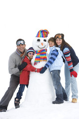Family of four embracing snowman in snow, smiling, portrait, cut out